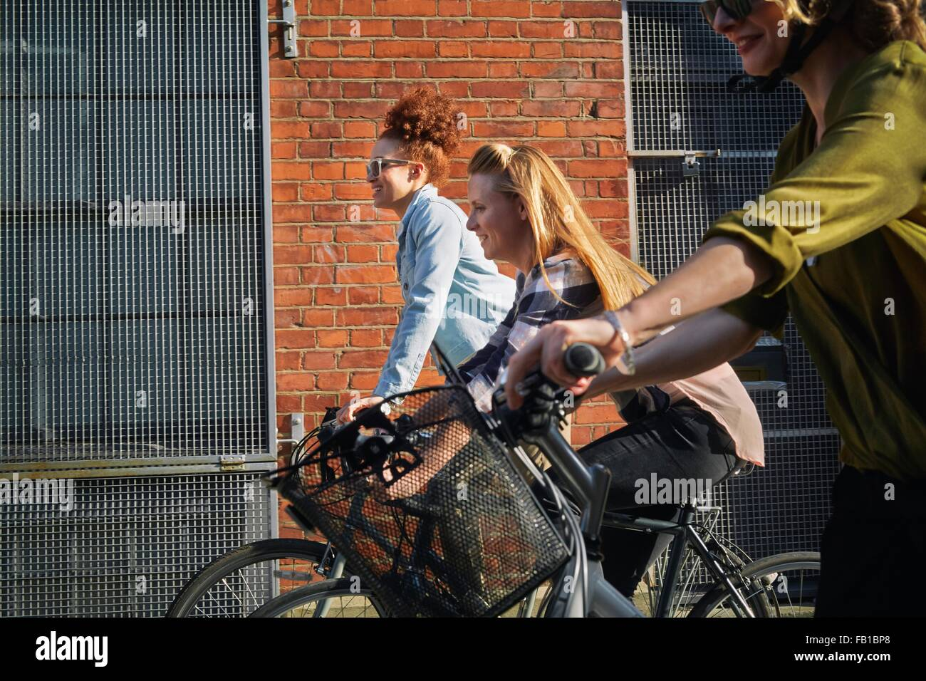 Side view of women cycling on bicycles past warehouse - Stock Image