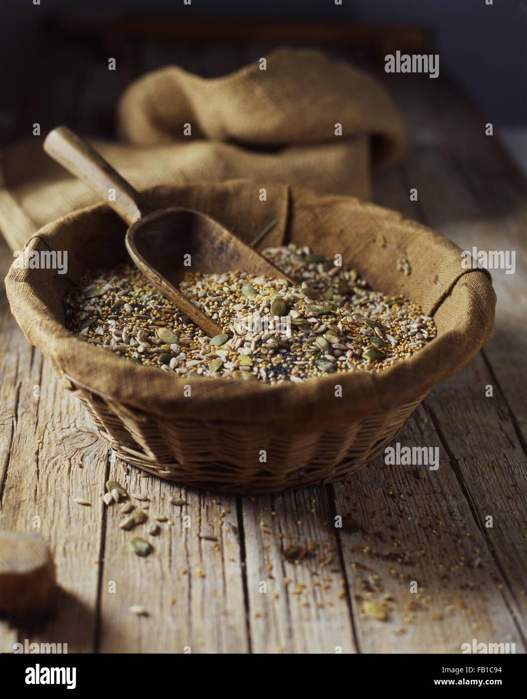 Organic mix of pumpkin, poppy, sunflower and flax seeds in wicker bowl - Stock Image