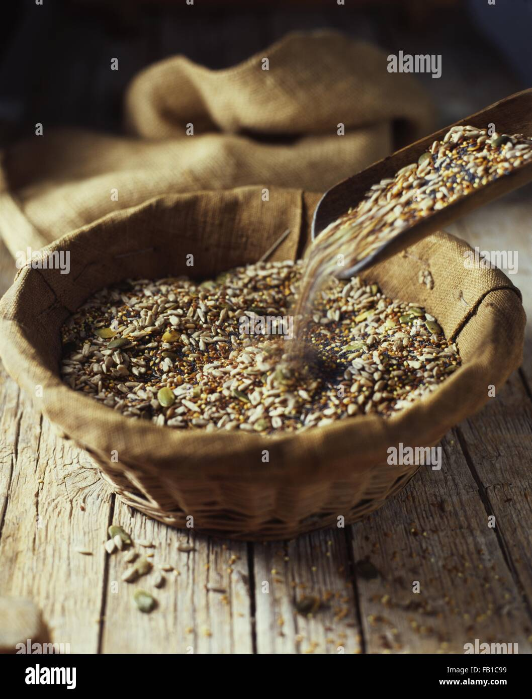 Organic bakery ingredients, mix of pumpkin, sunflower, poppy and flax seeds pouring into wicker bowl - Stock Image