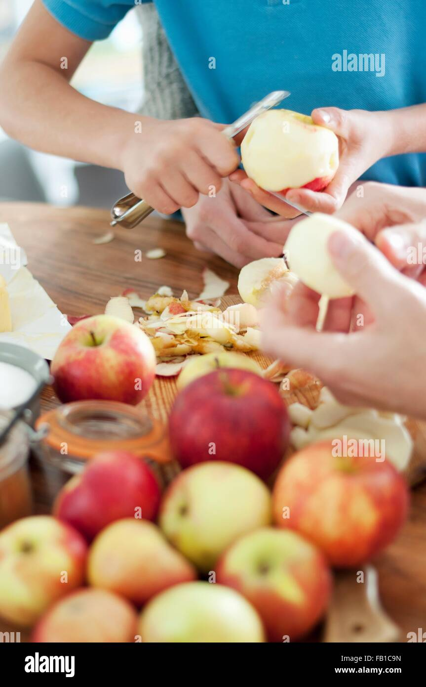 Cropped shot of father and sons hands peeling organic apples - Stock Image