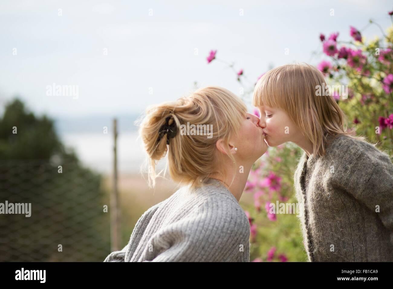 Mother kissing son in organic garden - Stock Image