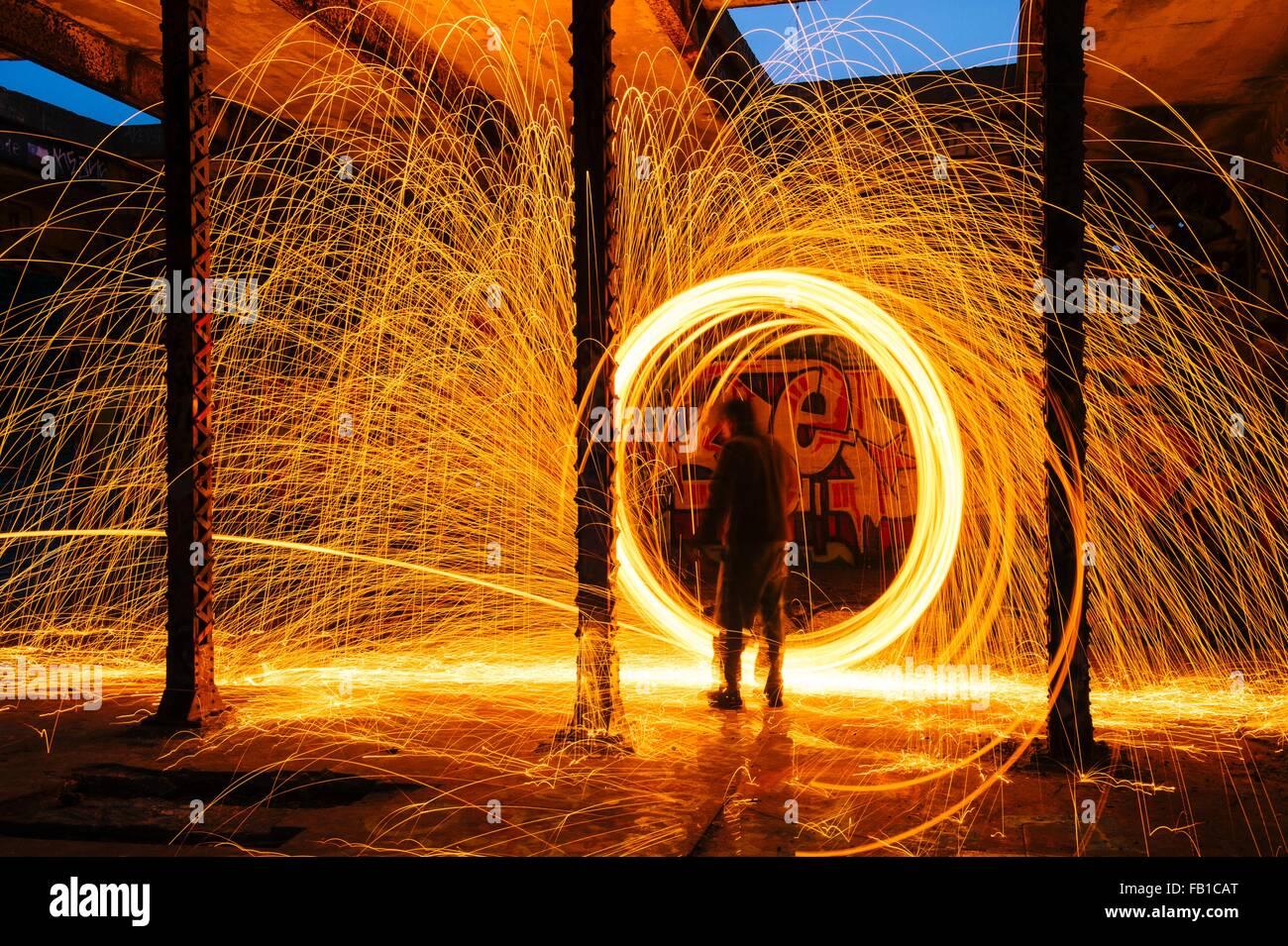 Man creating circular golden spark light trails in derelict building - Stock Image