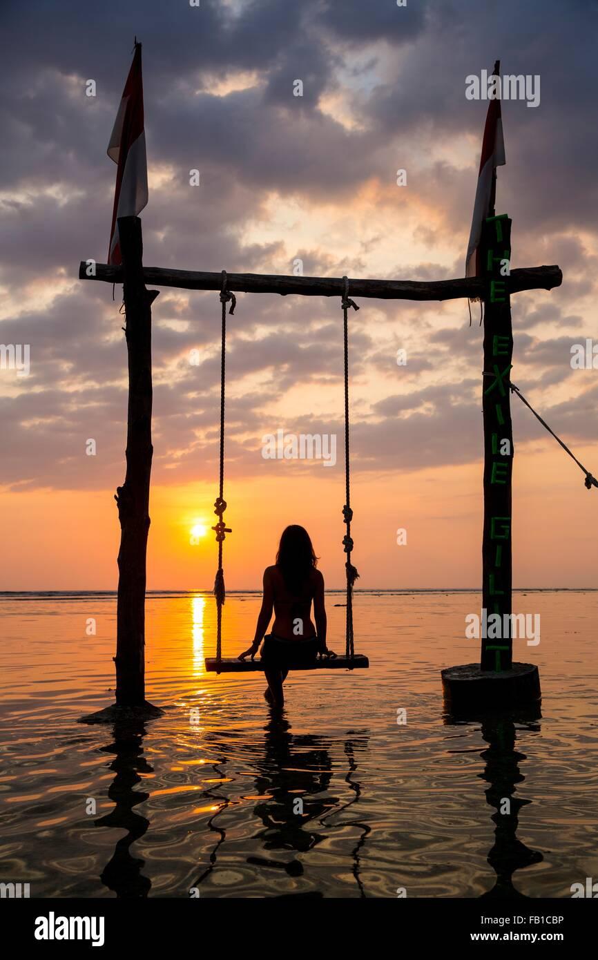 Silhouetted female tourist on swing watching sunset over sea, Gili Trawangan, Lombok, Indonesia - Stock Image
