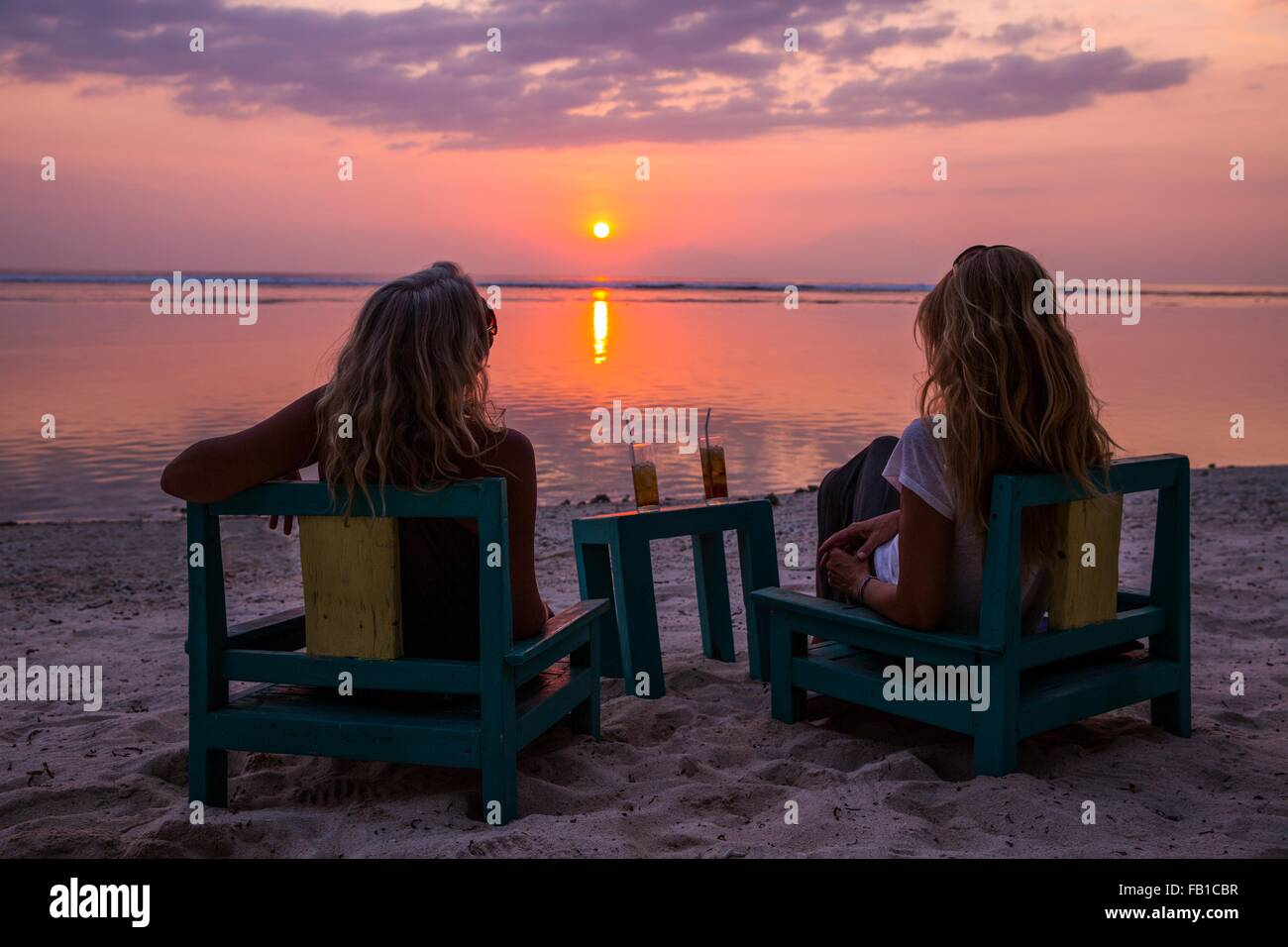 Silhouetted female tourists watching sunset over sea, Gili Trawangan, Lombok, Indonesia - Stock Image