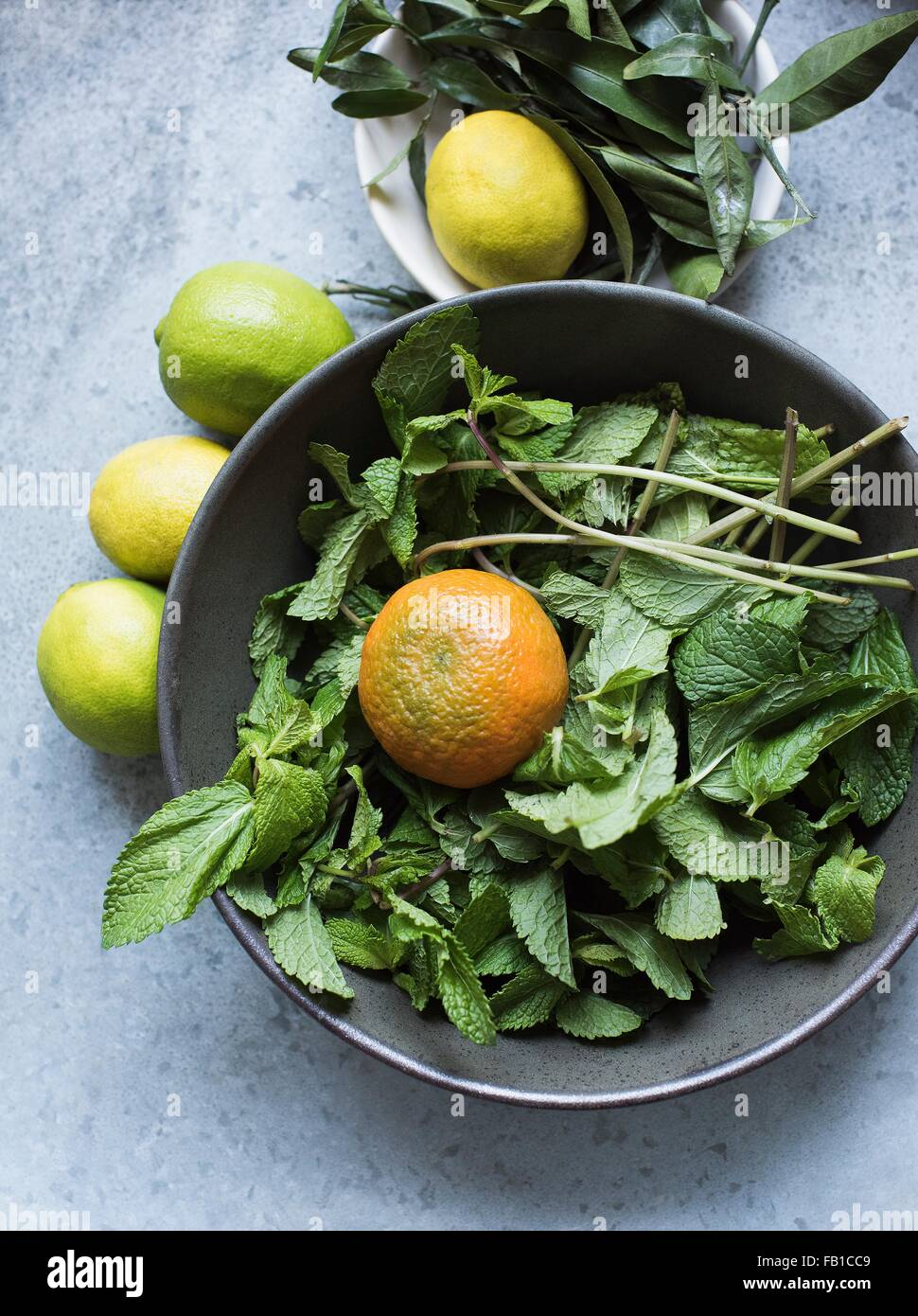Overhead view of mint leaves and citrus fruits in bowl Stock Photo