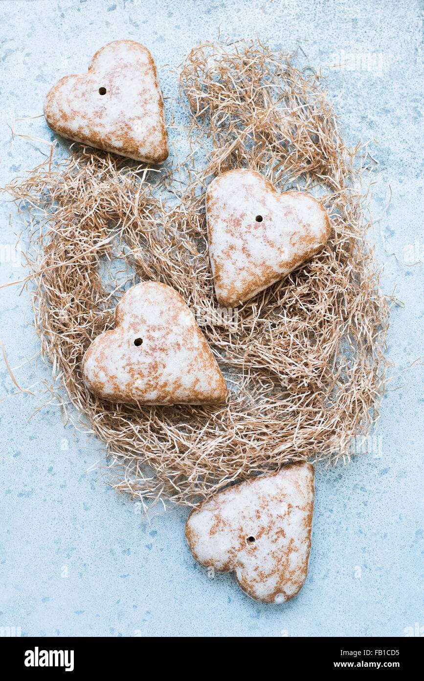 Overhead view of heart shaped gingerbread biscuits on straw - Stock Image