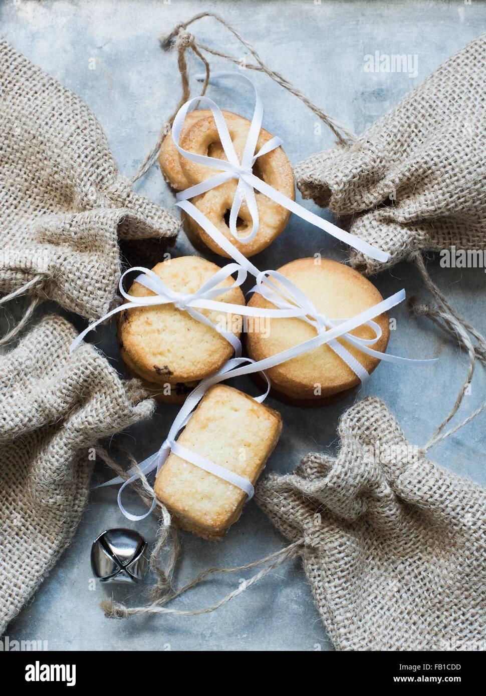 Overhead view of shortbread cookies tied with white ribbon and burlap bags Stock Photo