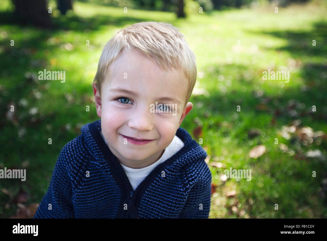 Portrait of blonde boy looking at camera smiling - Stock Image