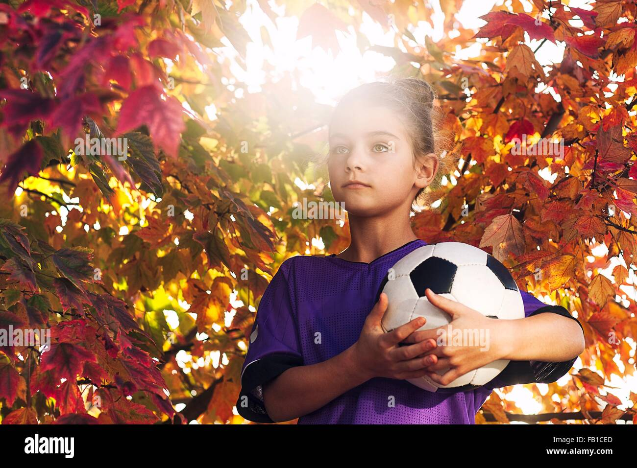 Girls by tree covered in autumn leaves holding football looking away - Stock Image