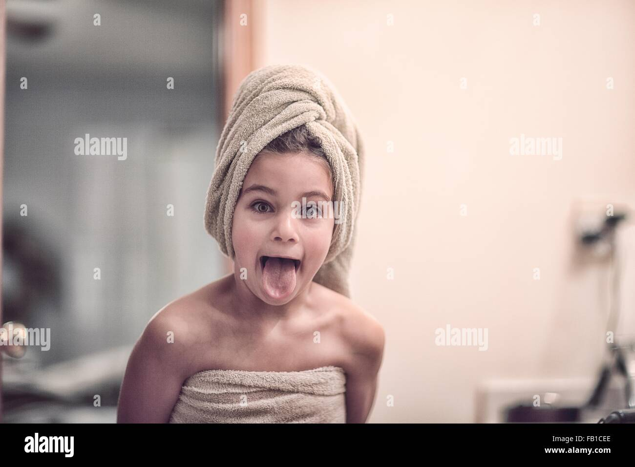 Girl wrapped in towel wearing towel on head looking at camera sticking out tongue - Stock Image