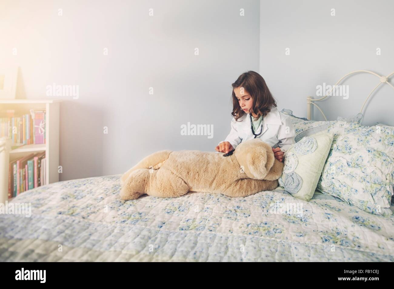 Girl dressed up in lab coat sitting in bed using stethoscope on soft toy - Stock Image