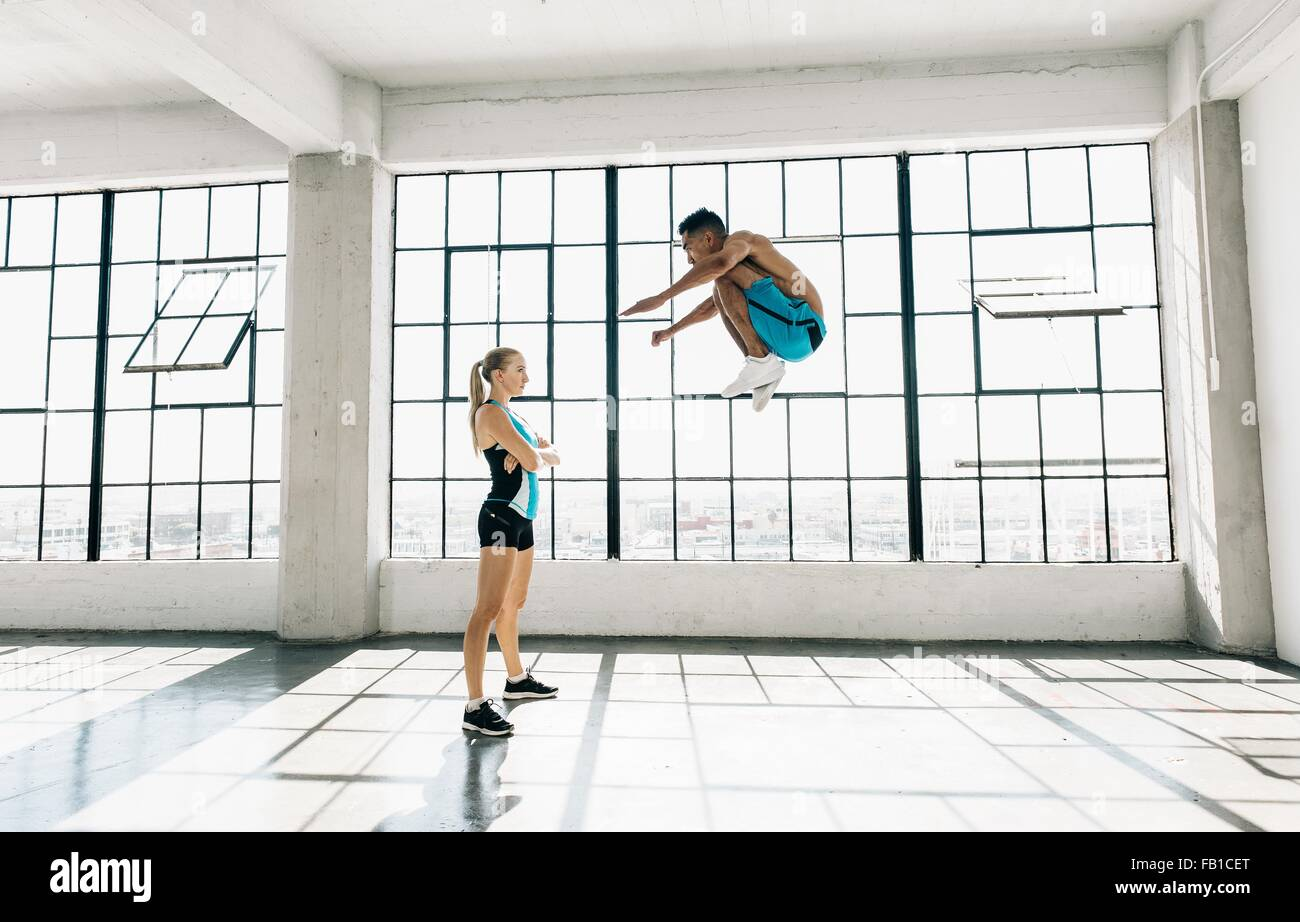 Side view of man in gym jumping in mid air, bent knees - Stock Image