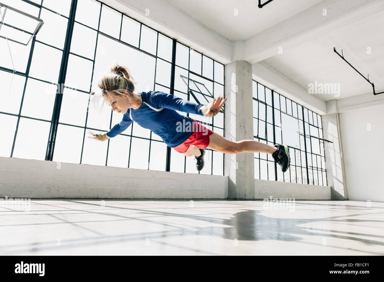Low angle view of young woman in gym doing mid air push up - Stock Image