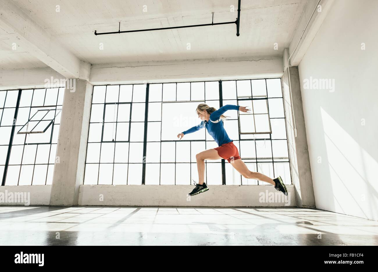 Side view of young woman in gym doing powerful mid air running stance - Stock Image