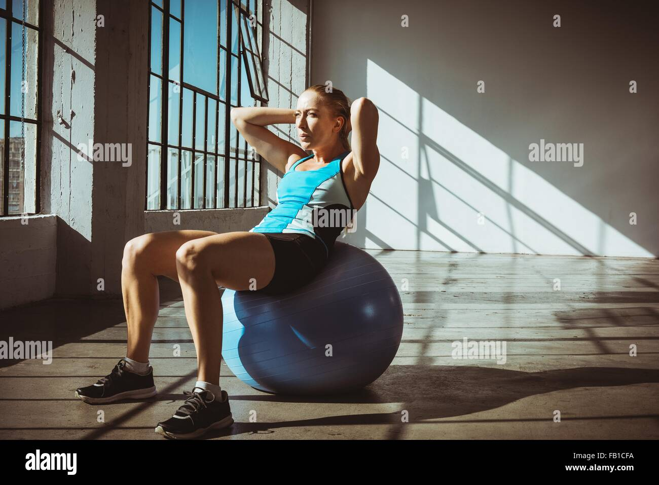 Young woman in gym sitting on exercise ball hands behind head, looking away - Stock Image