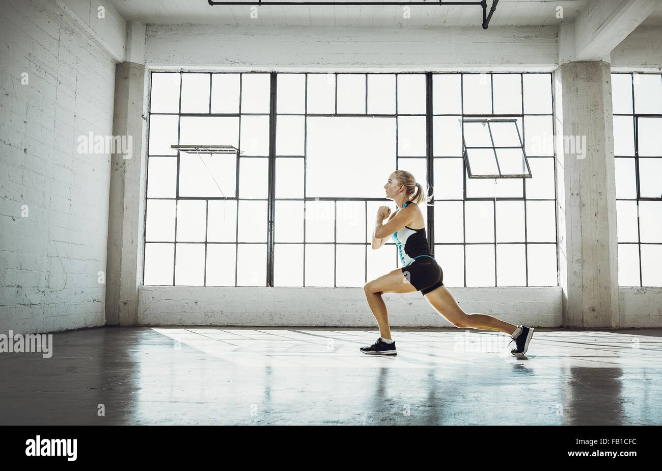 Side view of young woman in gym doing lunge - Stock Image