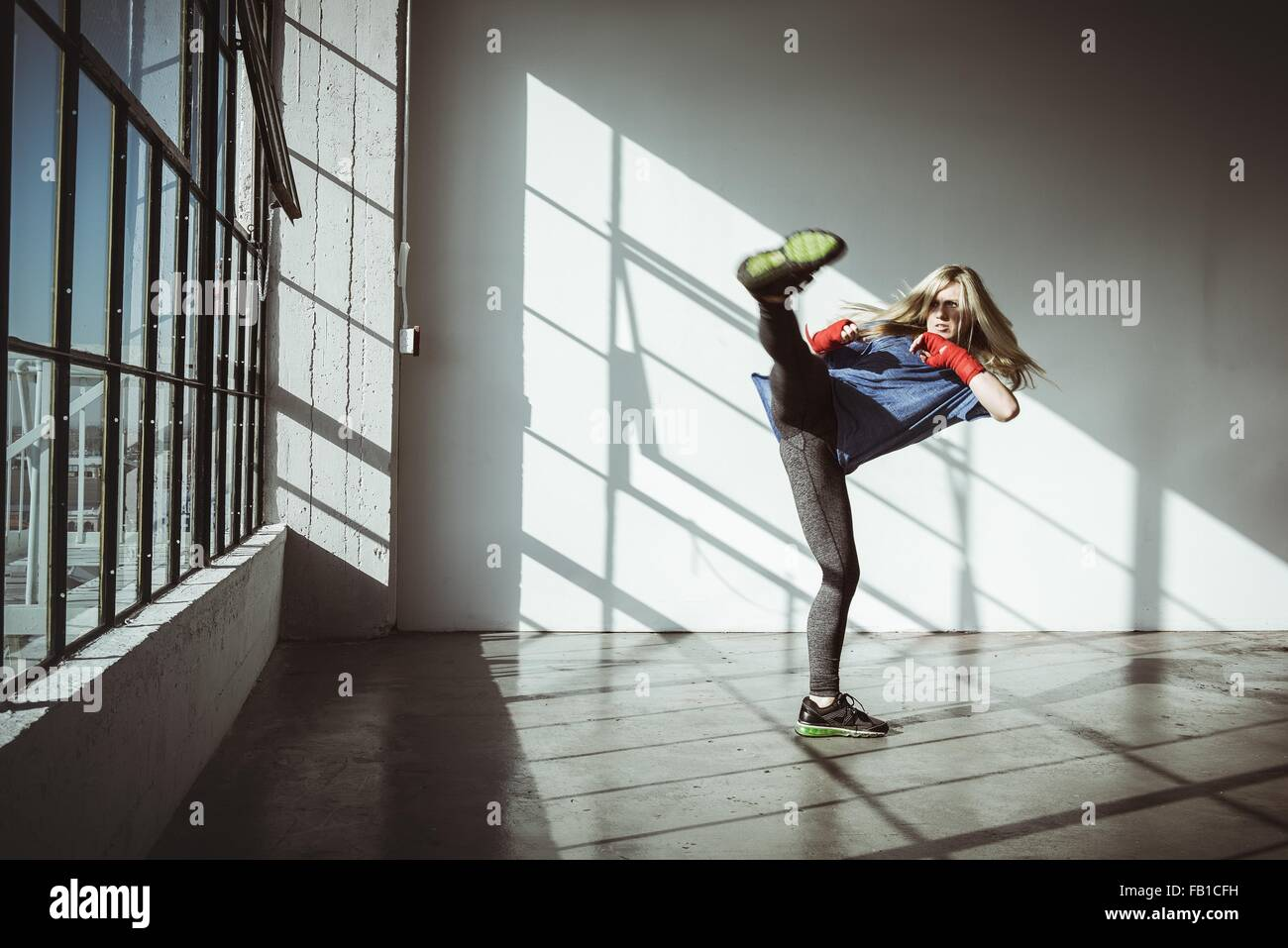Full length front view of young woman in gym in kickboxing stance looking away - Stock Image