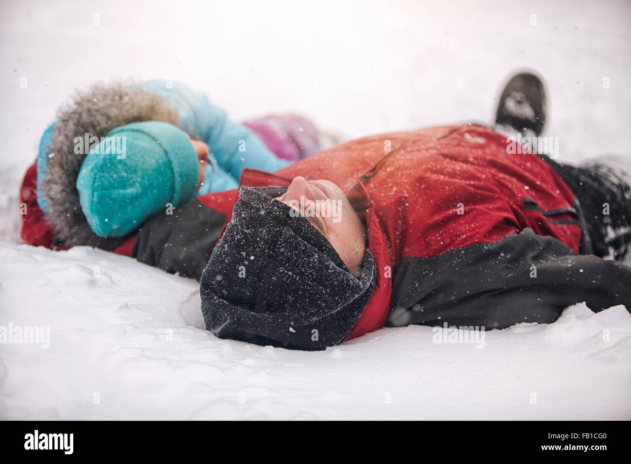 Father and daughter wearing knit hats lying on backs in snow - Stock Image