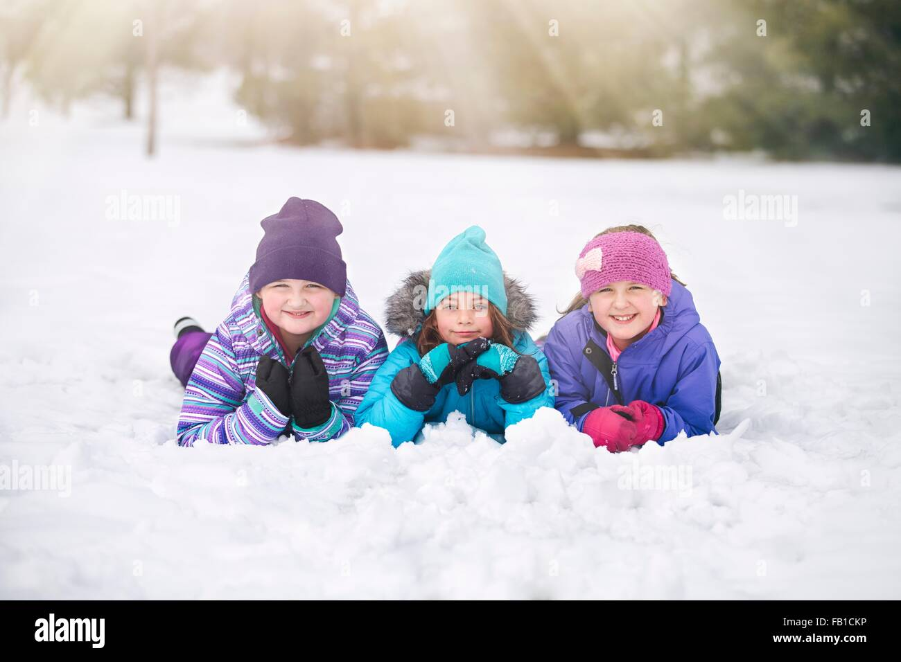 Friends wearing knit hats lying on front side by side in snow looking at camera smiling - Stock Image