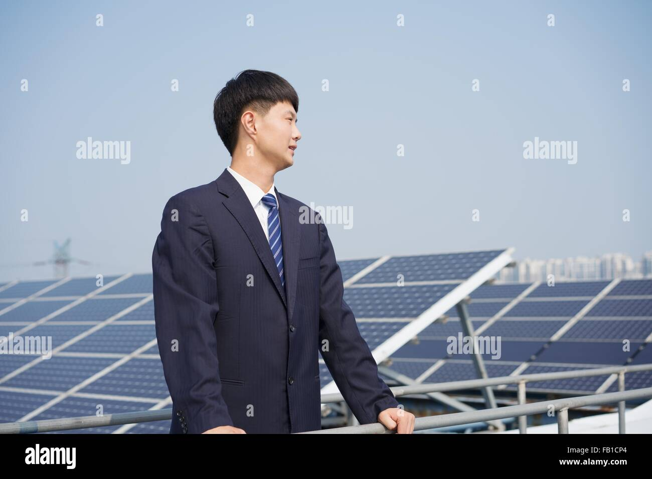 Businessman on roof of solar panel assembly factory, Solar Valley, Dezhou, China - Stock Image