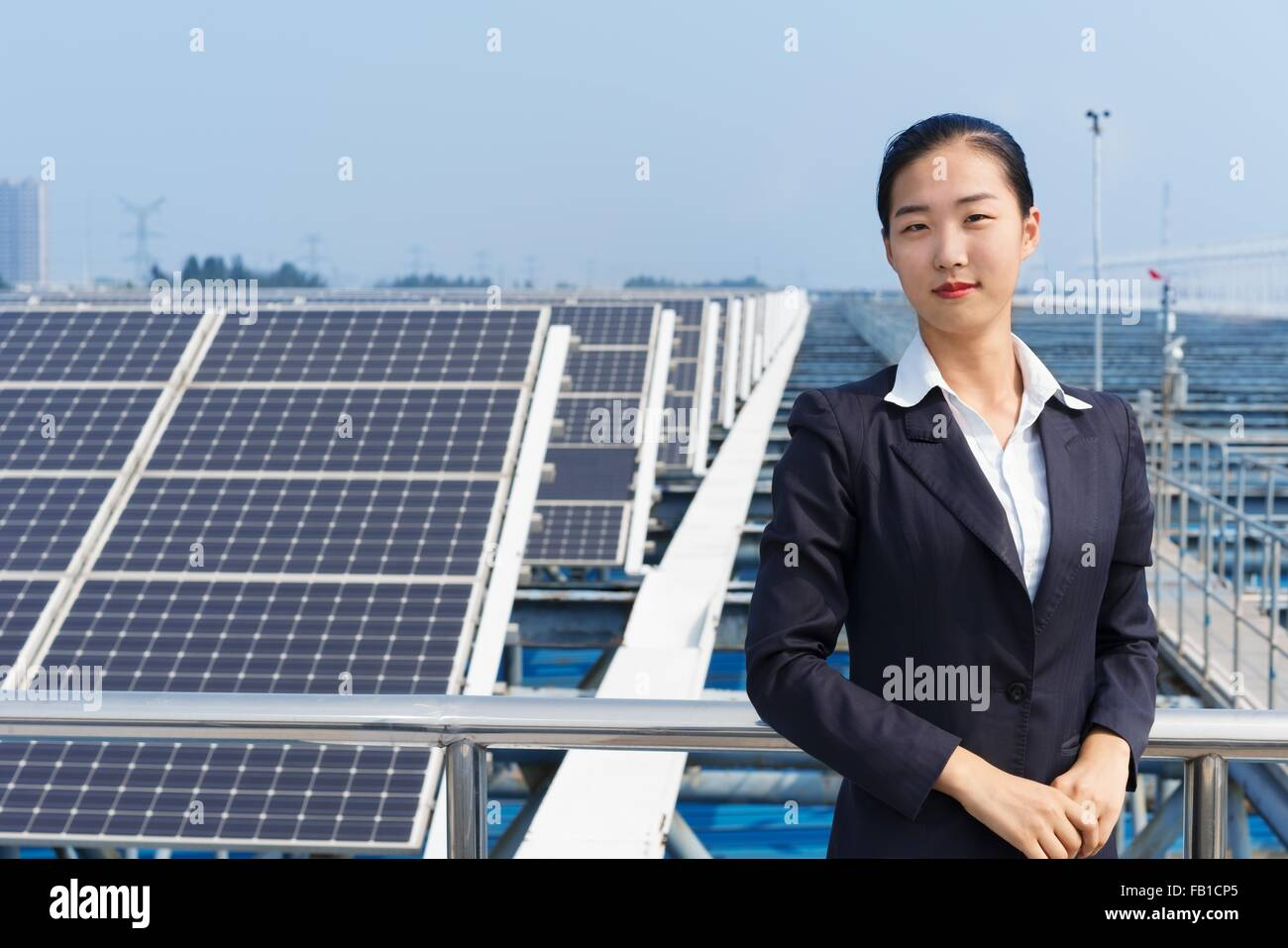 Businesswoman on roof of solar panel assembly factory, Solar Valley, Dezhou, China - Stock Image