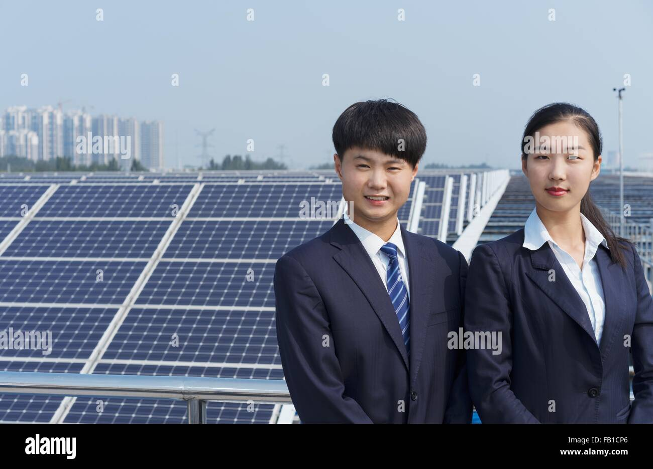 Businessman and businesswoman on roof of solar panel assembly factory, Solar Valley, Dezhou, China - Stock Image