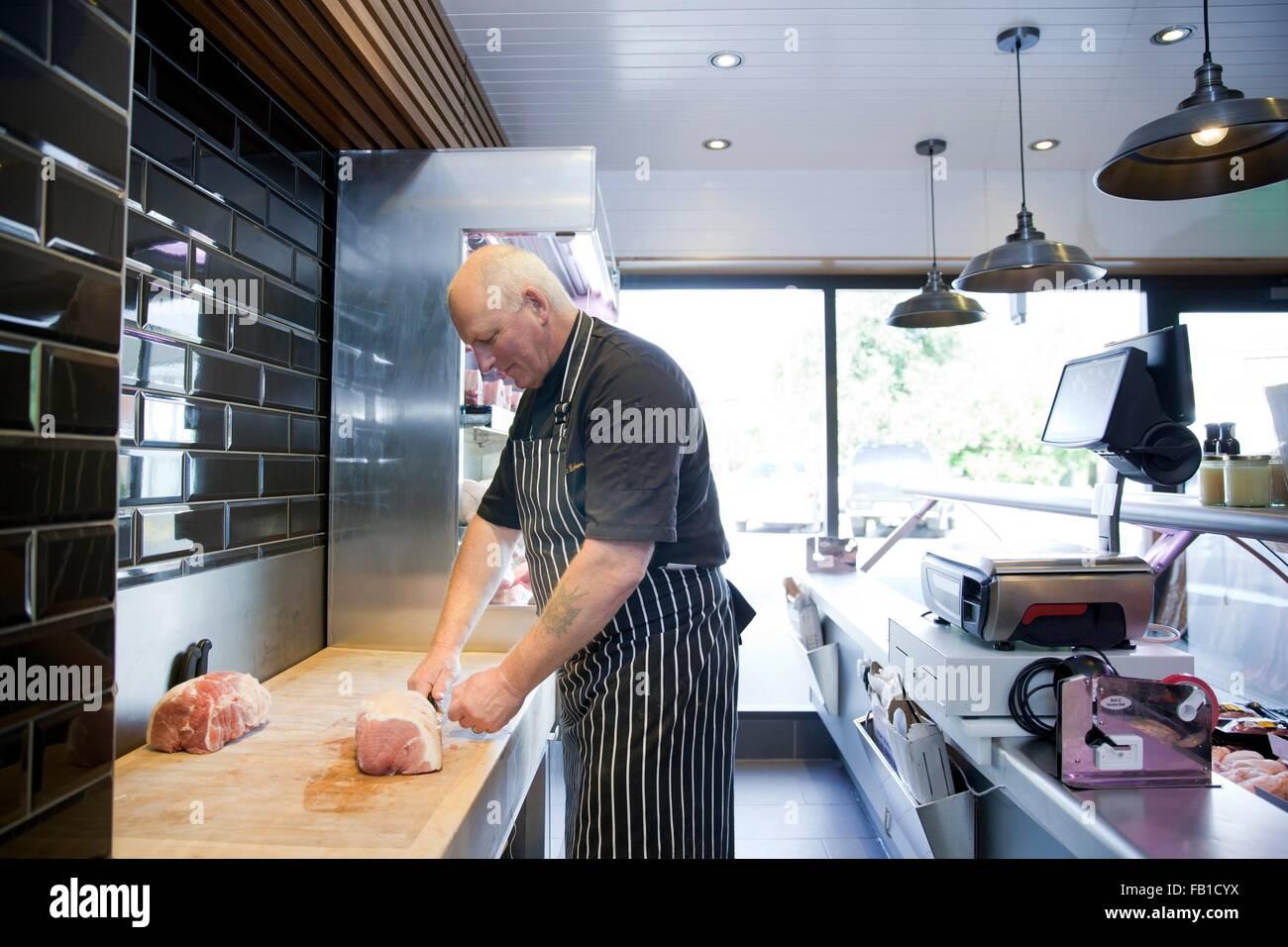 Mature butcher preparing meat in butchers shop - Stock Image