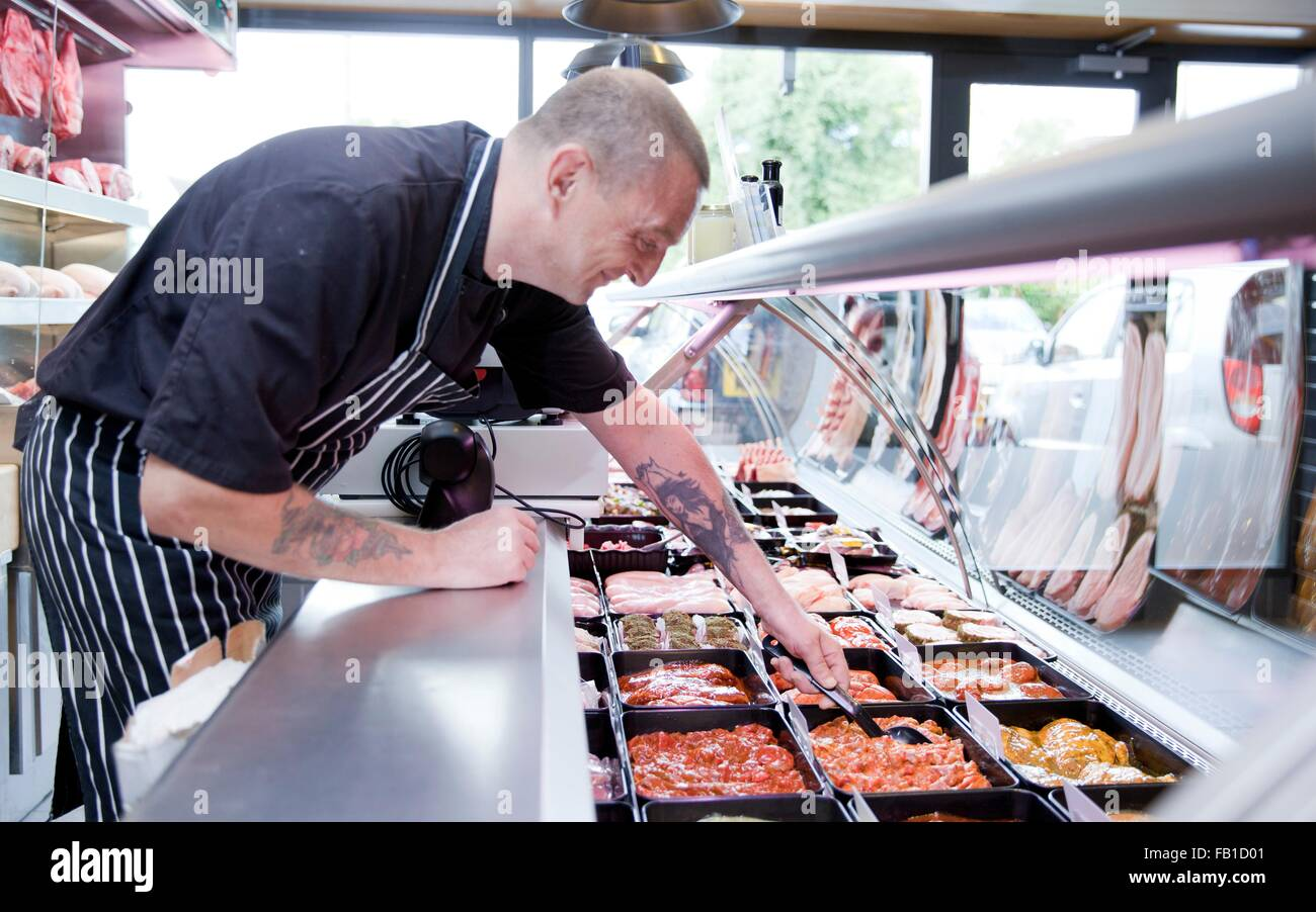 Butcher serving fresh food from refrigerator in butchers shop - Stock Image
