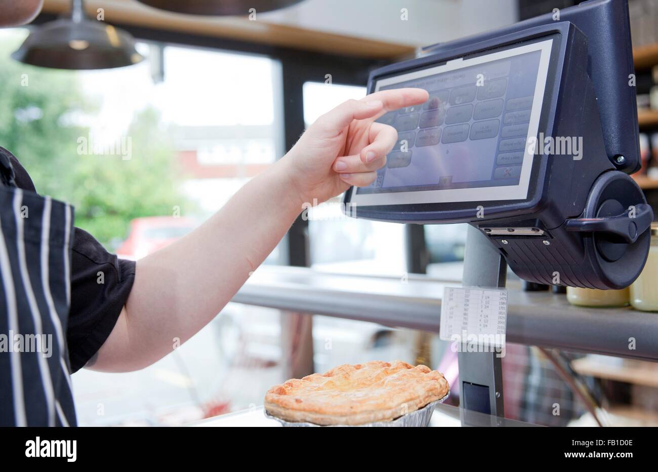 Cropped shot of butcher weighing pie in butchers shop - Stock Image