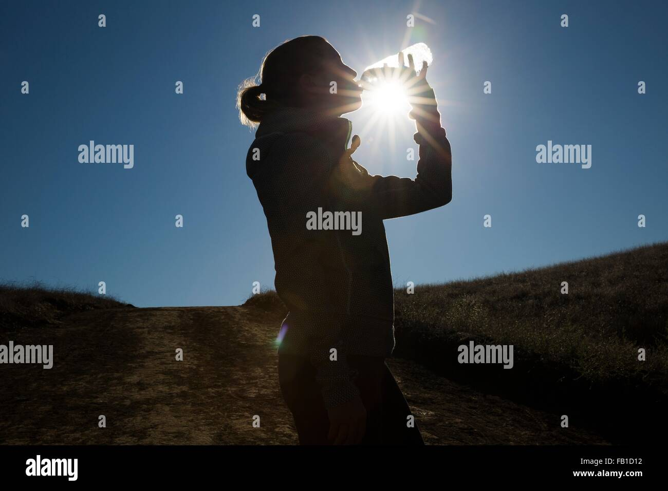 Silhouetted female runner drinking from water bottle - Stock Image