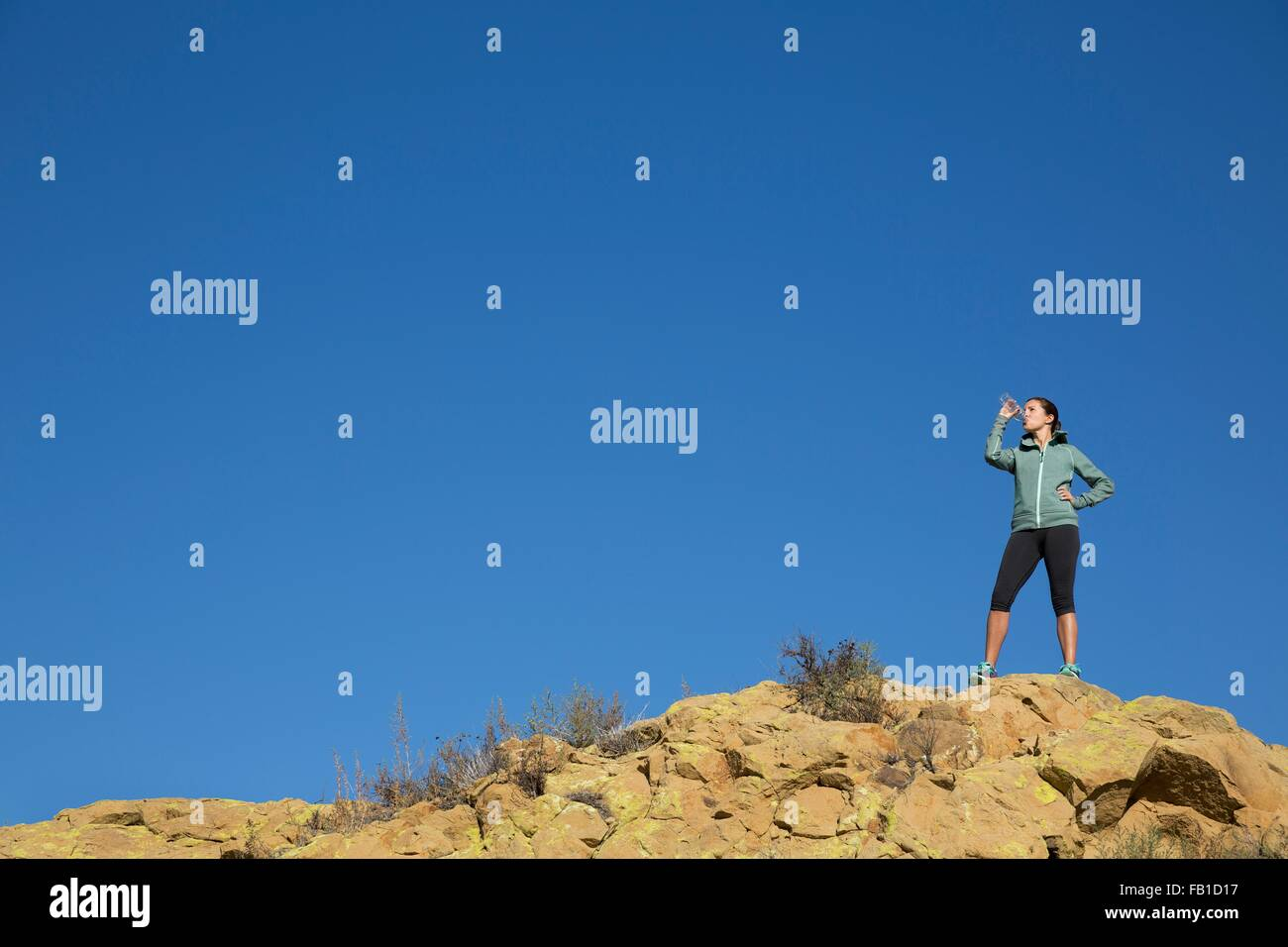 Female runner drinking from water bottle on rugged hill - Stock Image