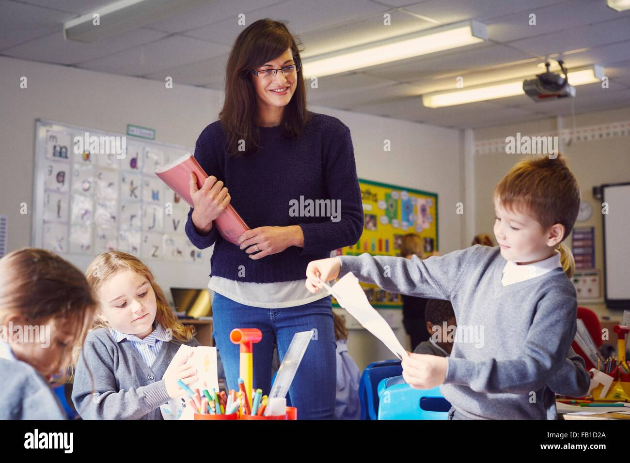 Female teacher with children drawing in elementary school classroom - Stock Image