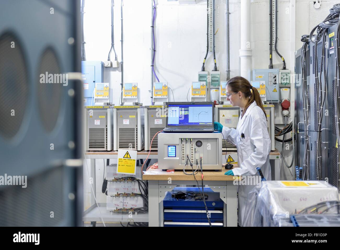 Female scientist with battery aging test equipment in battery research facility - Stock Image