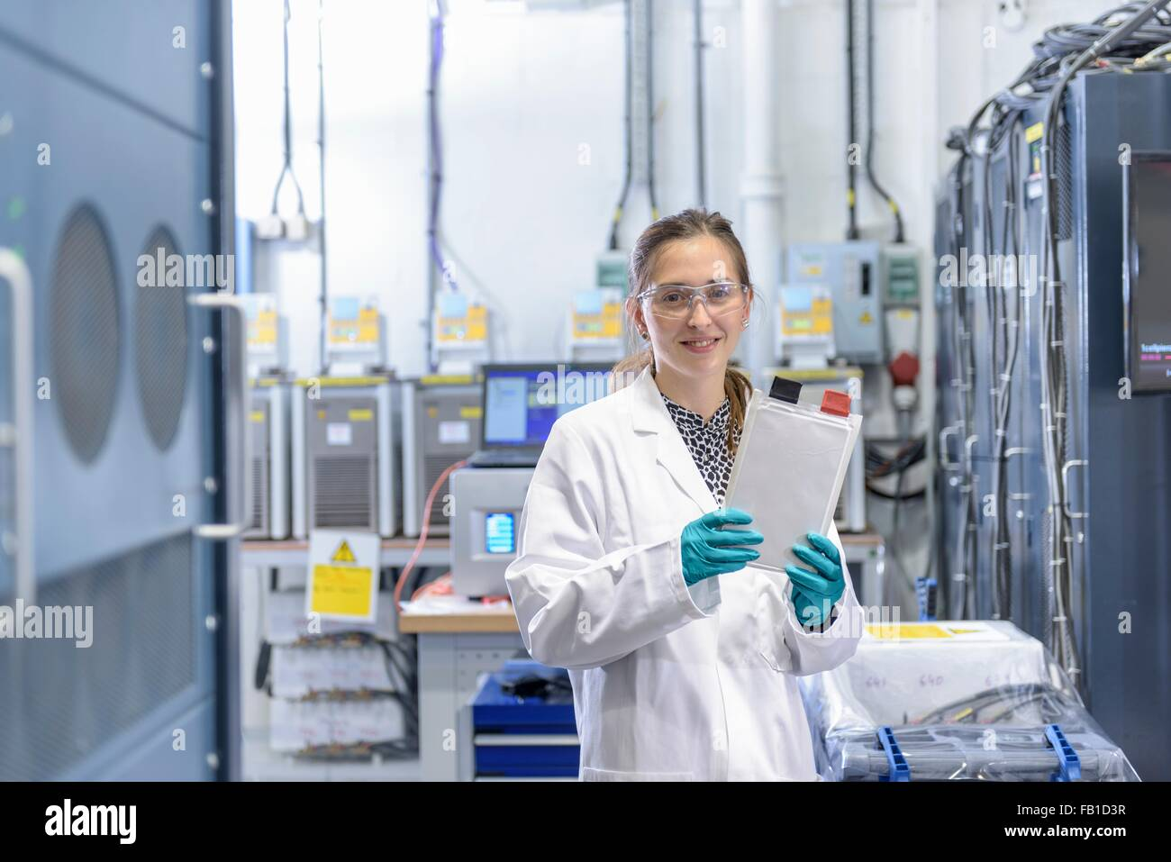 Portrait of female scientist holding lithium ion pouch battery in battery research facility - Stock Image