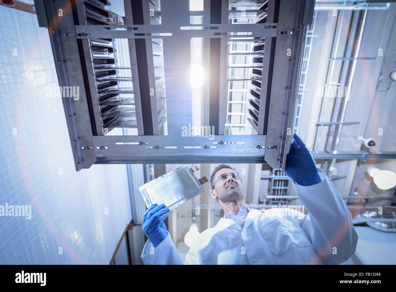 Scientist with lithium ion pouch cell manufacture machine in battery research facility, low angle view - Stock Image