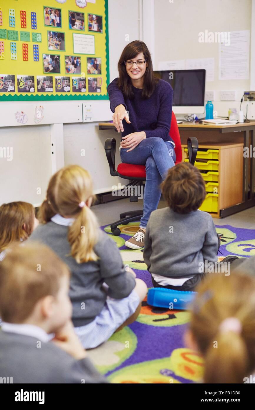 Teacher pointing to children sitting on floor in elementary school classroom - Stock Image