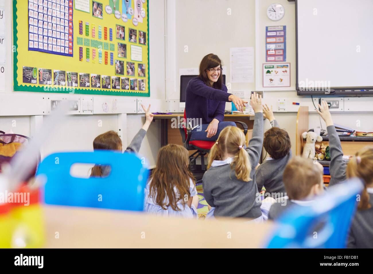 Teacher questioning children sitting on floor in elementary school classroom - Stock Image