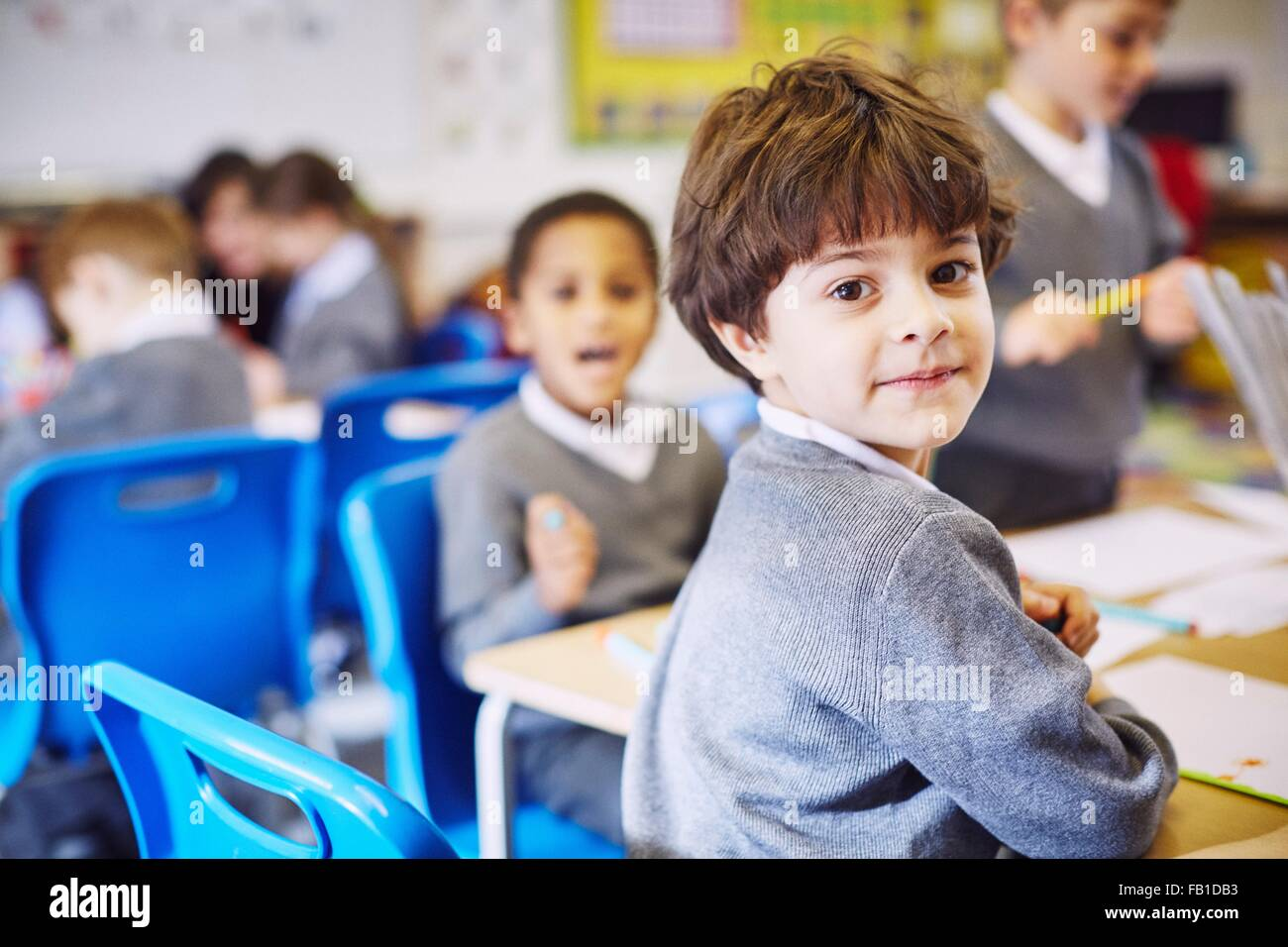 Portrait of boy looking over his shoulder in elementary school classroom - Stock Image