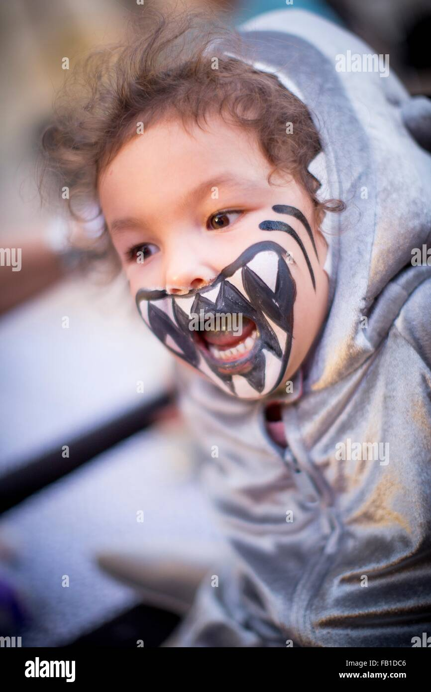 Angled view of girl dressed as shark, teeth painted on face, mouth open looking away - Stock Image