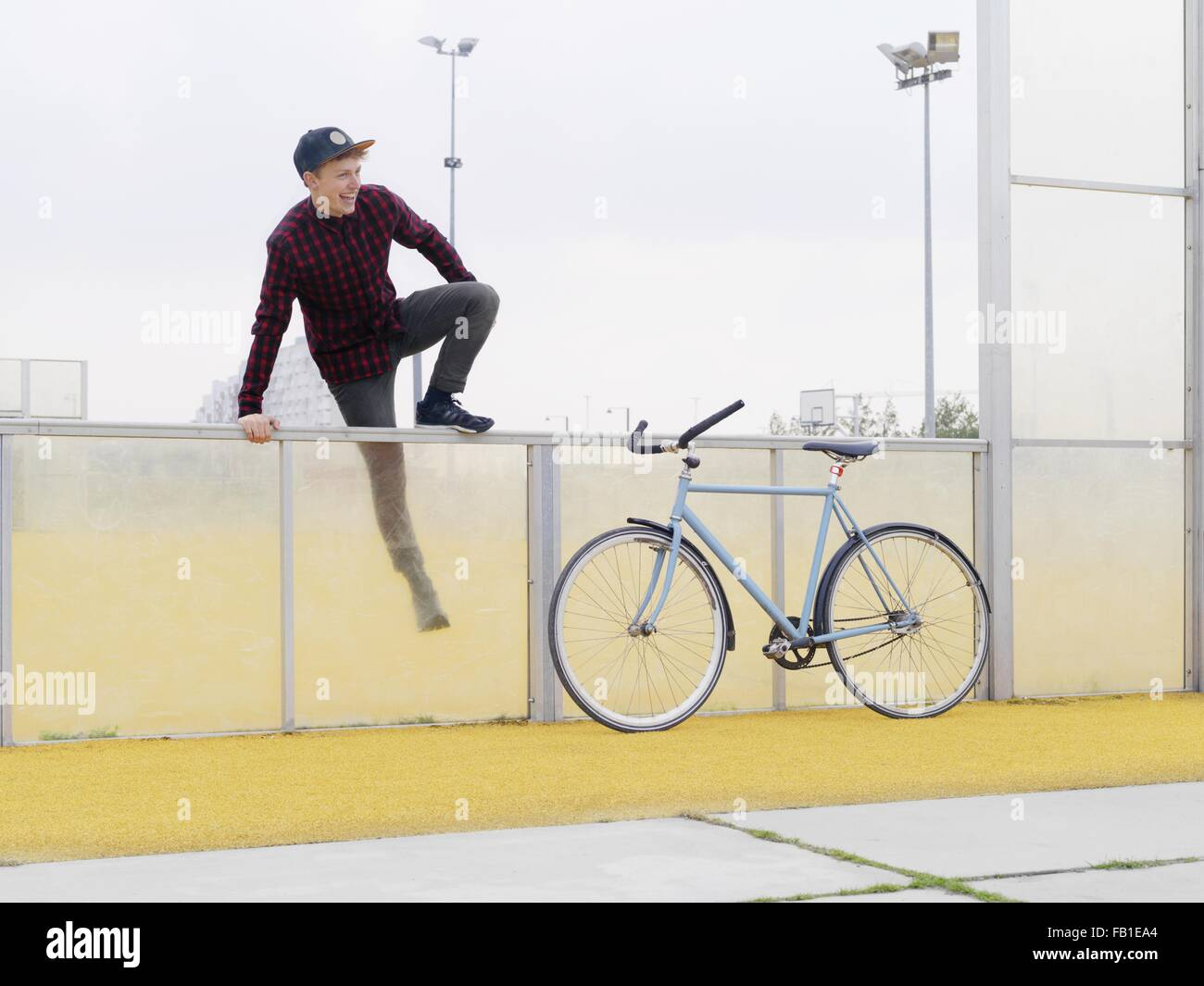 Urban cyclist climbing over fence on sports field - Stock Image