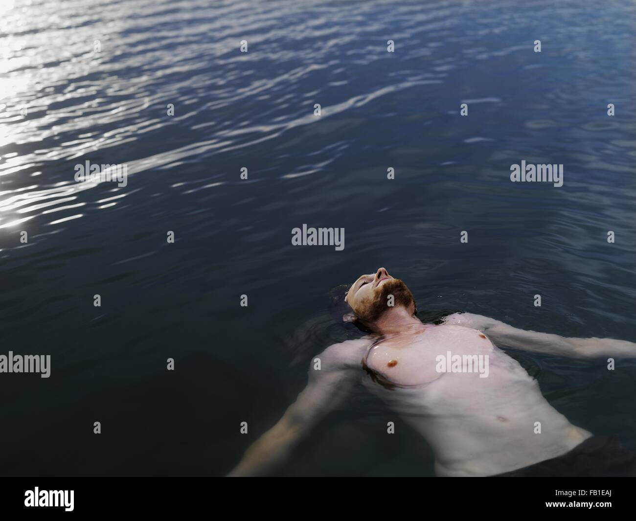 High Angle View Of Young Man Floating On Back In Water Arms Outstretched Looking Up
