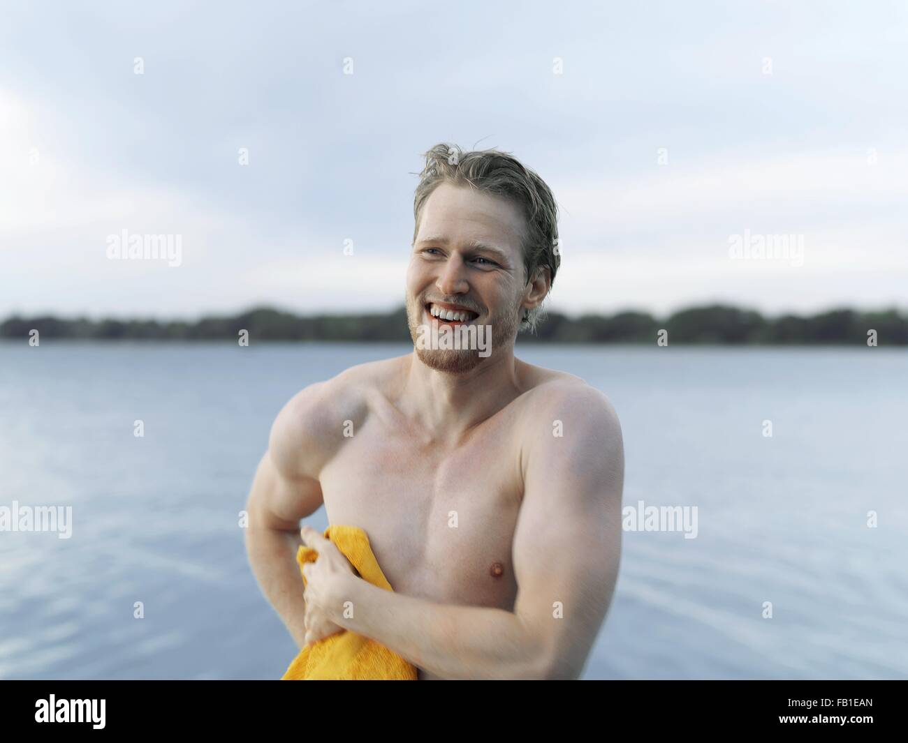 Bare chested young man drying off with towel, looking away smiling, Copenhagen, Denmark - Stock Image