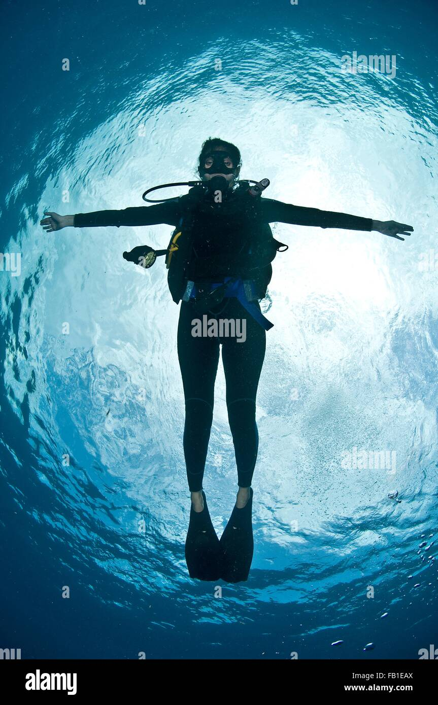 Full length view scuba diver arms open floating water surface camera Chinchorro Atoll Quintana Roo Mexico - Stock Image