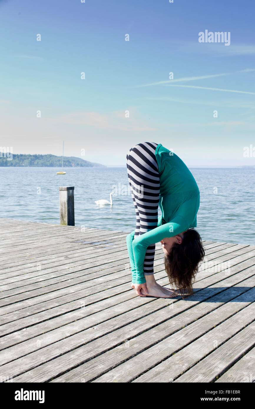 Side view of mature woman on pier by ocean bending over holding ankles - Stock Image