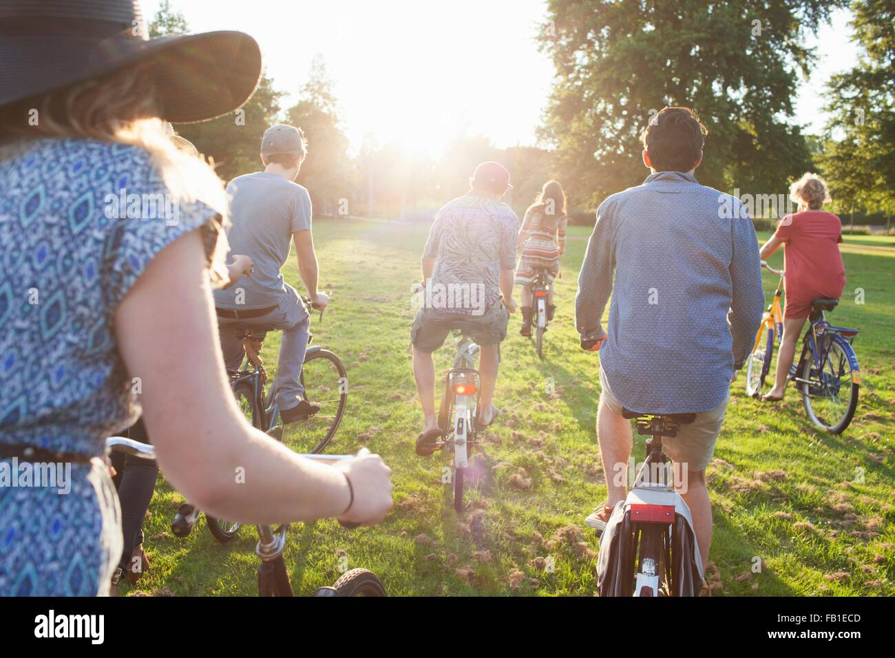 Rear view of party going adults arriving in park on bicycles at sunset - Stock Image