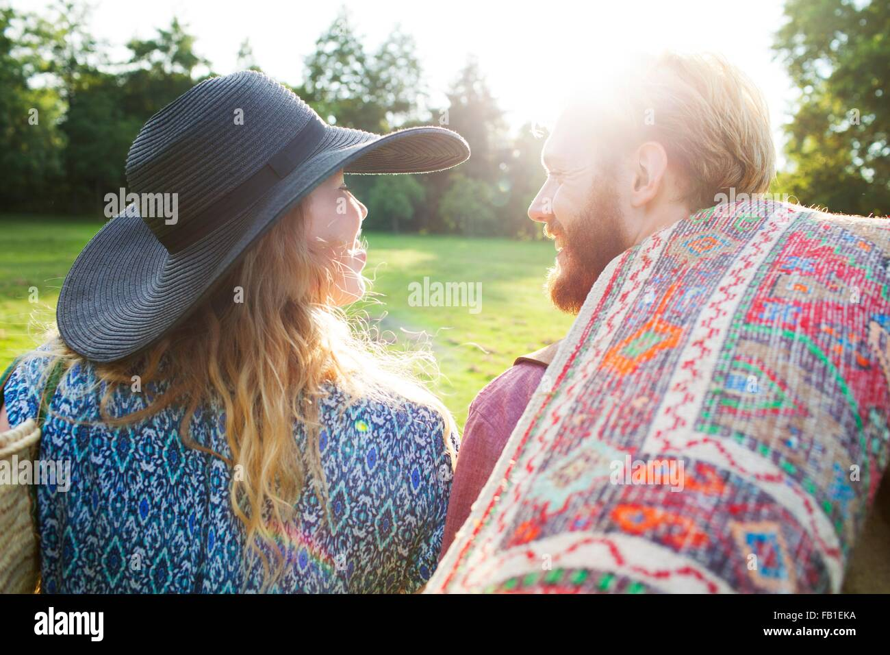 Rear view of romantic young couple carrying rug for picnic in park - Stock Image