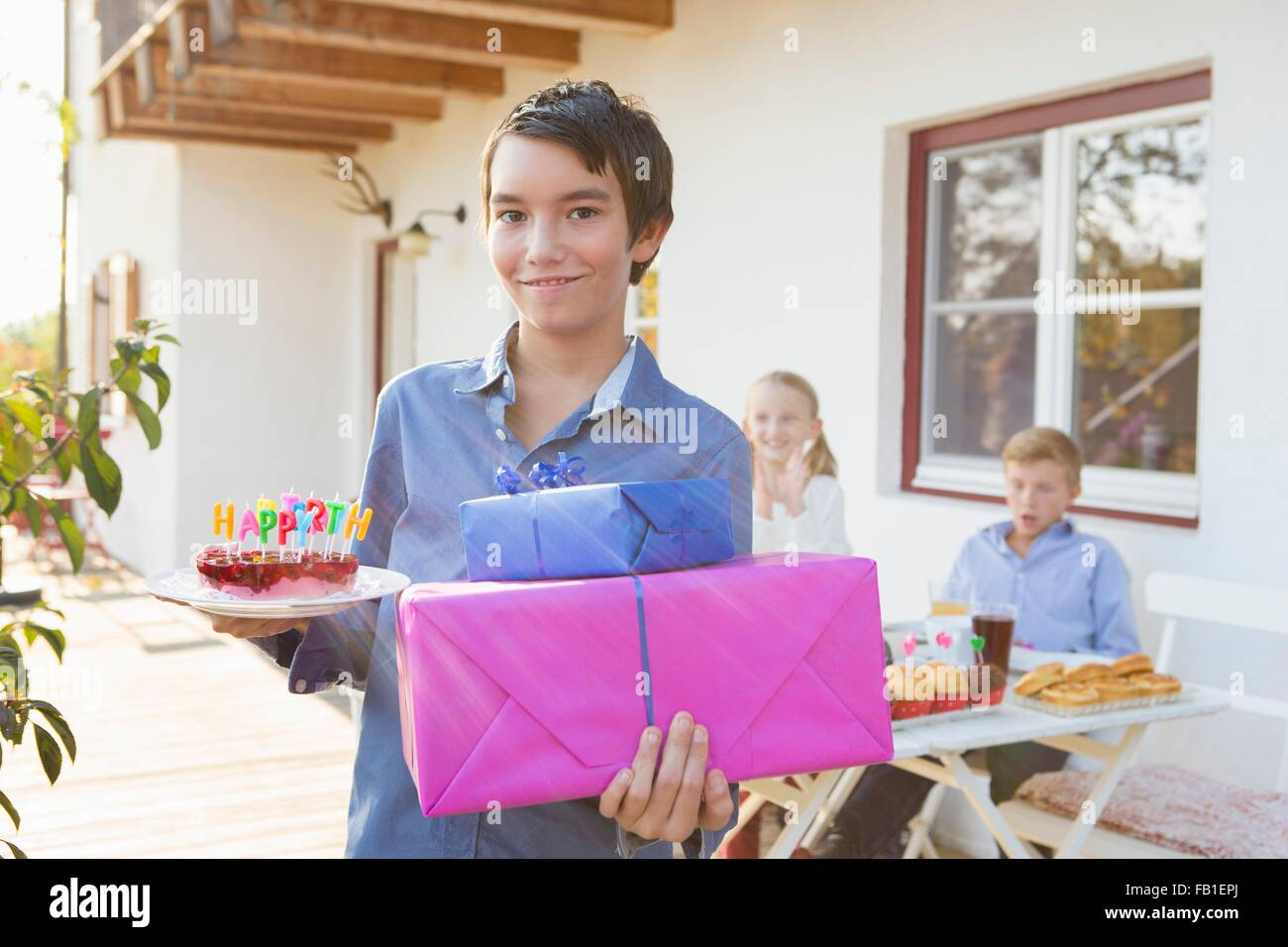 Portrait Of Teenage Boy Carrying Birthday Cake And Gifts On Patio