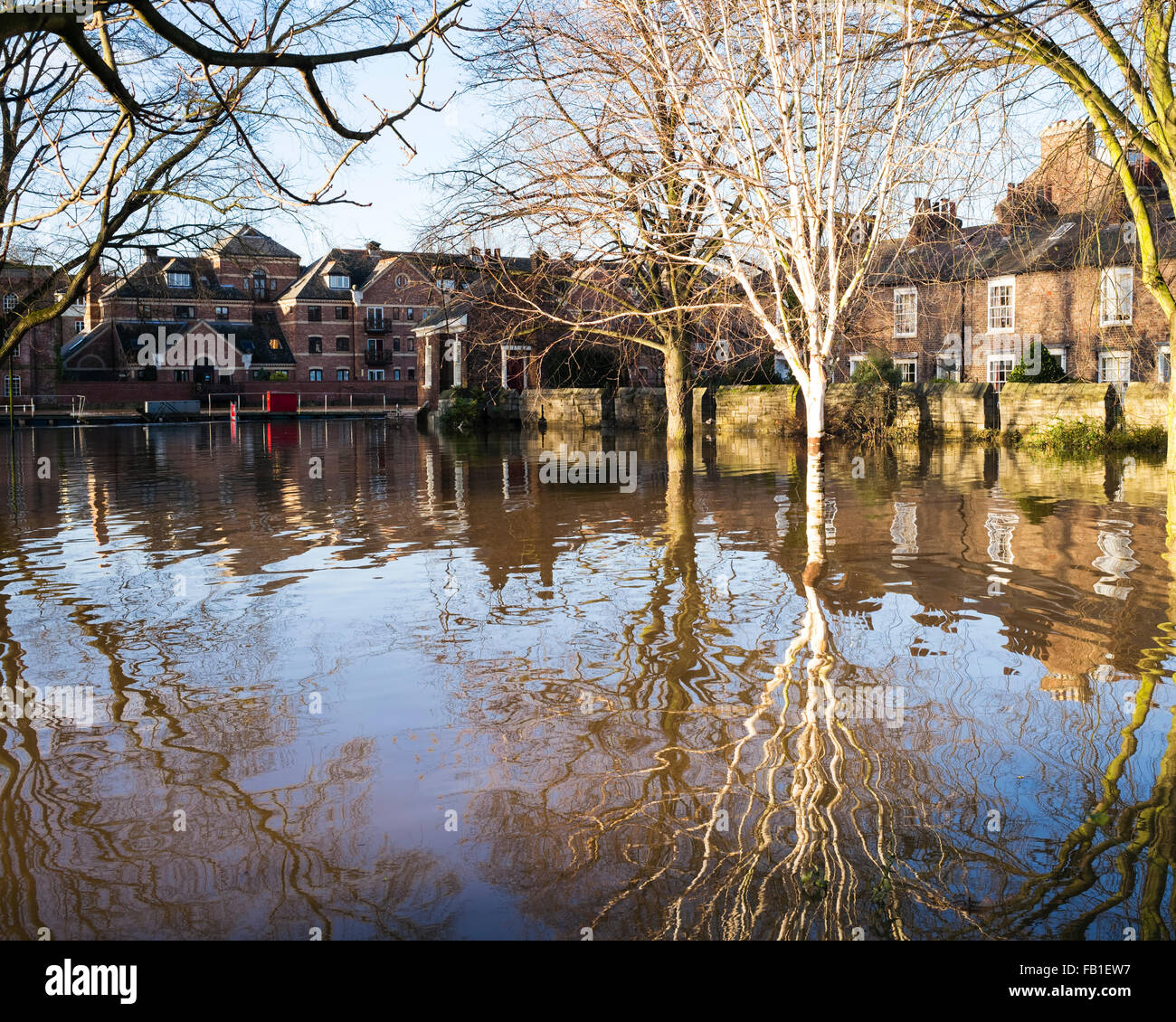 Modern Skeldergate apartments and a medieval wall reflected in floodwater in St. George's Field Park, York, Yorkshire, Stock Photo