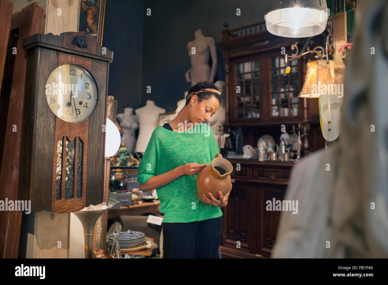 Young woman looking at jug price ticket in vintage shop - Stock Image