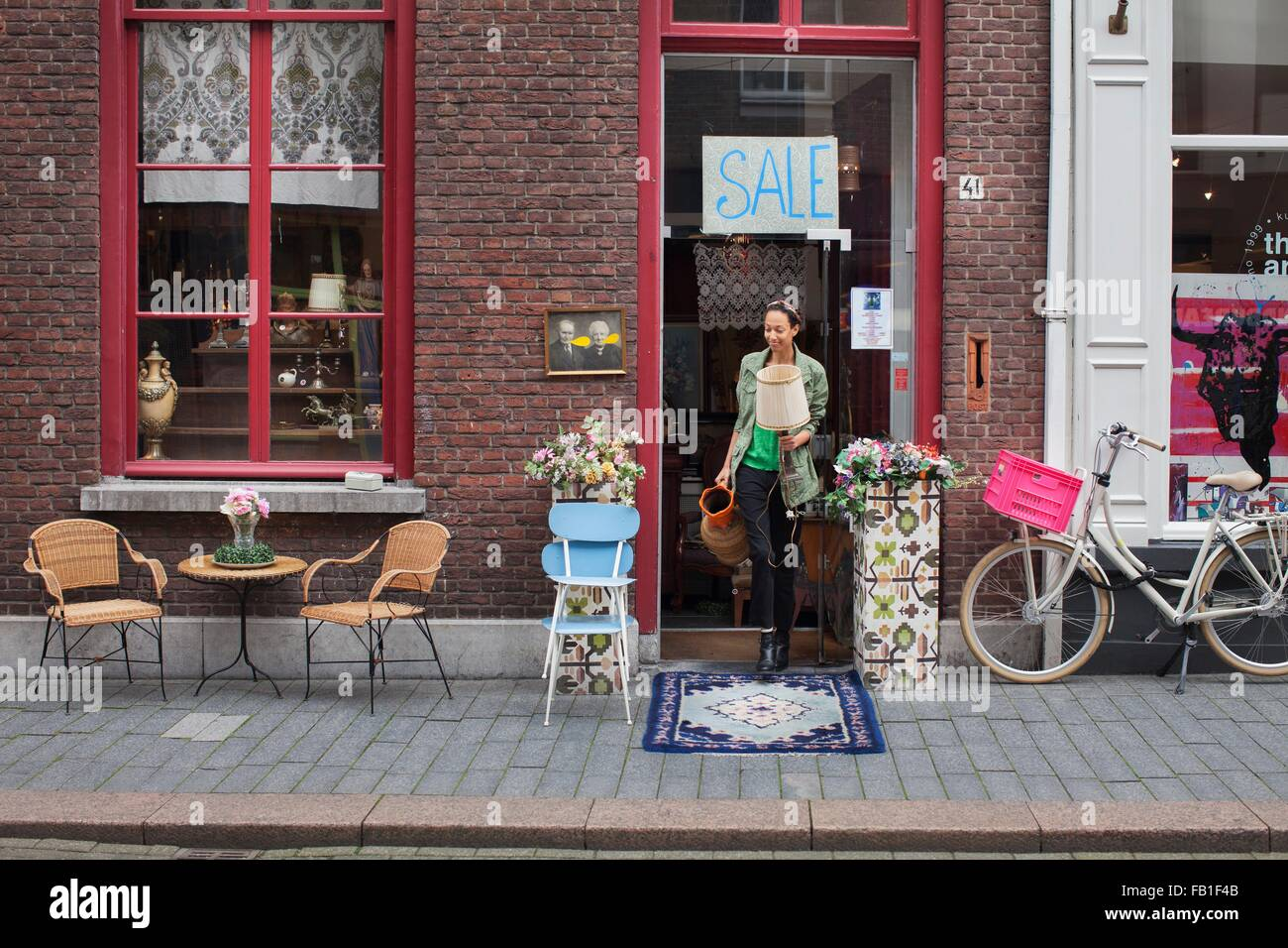 Young female customer with jug and lamp outside vintage shop - Stock Image